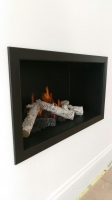 Hole in the wall fireplace with black fire chamber and four sided black frame