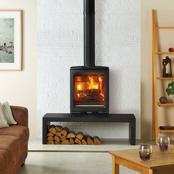 wood burning stove on a table with logs stacked underneath in a stylishly clean white room