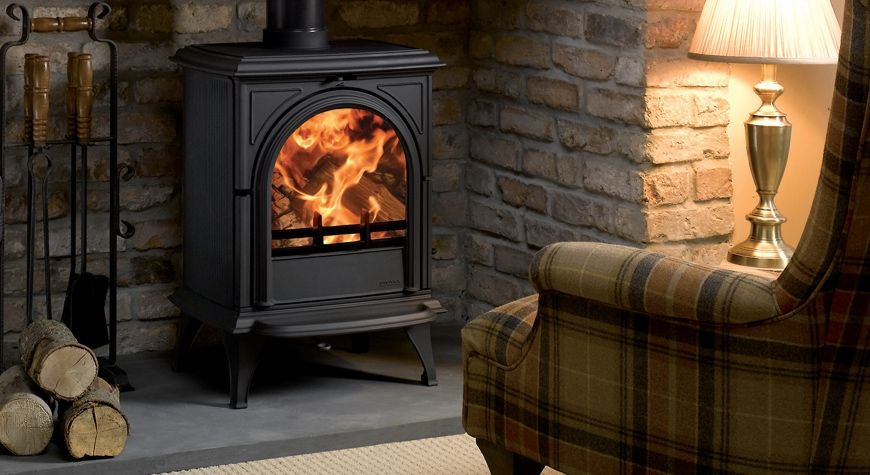 wood burning stove in living room in front of sofa