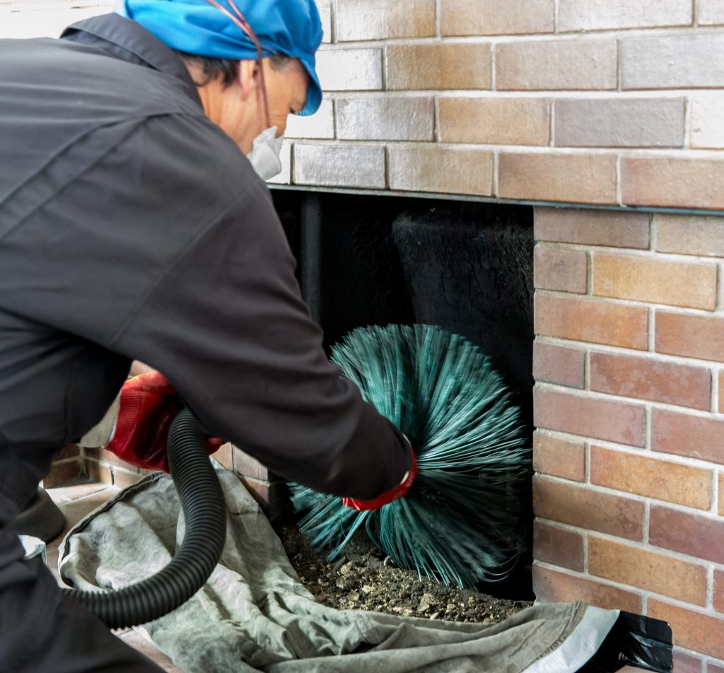 Chimney sweep wearing a mask for protection whilst cleaning chimney