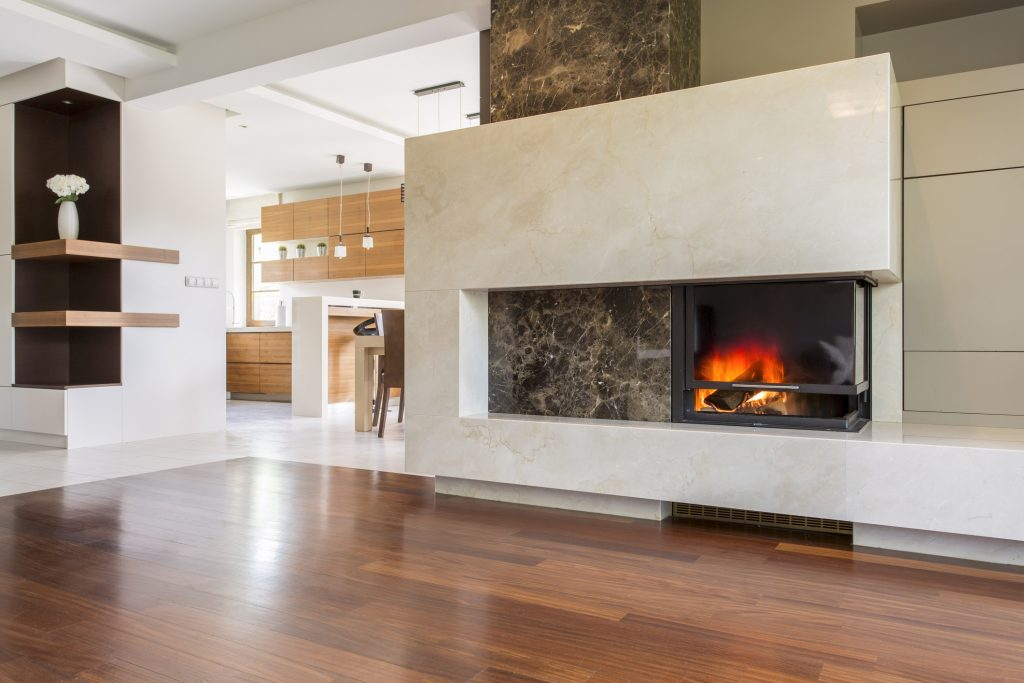 Marble fireplace in a vast living room with panelled floor, joined with bright kitchen